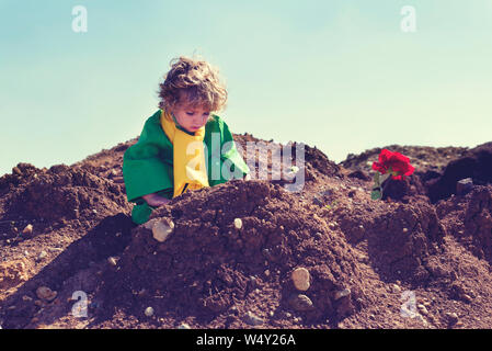 Cute boy with curly blond hair playing above pile of earth wearing green clothes and yellow scarf Selective focus - Stock Photo