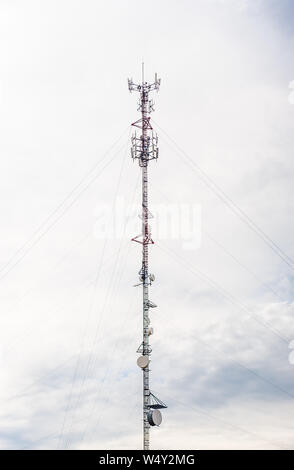Tall red and white metal communications antenna tower with dishes and supporting cables, against cloudy gray sky. - Stock Photo