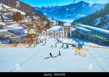 ZELL AM SEE, AUSTRIA - FEBRUARY 28, 2019: Exciting journey on modern cable car with a view on its lower station, skiers on Shcmitten mount pistes, Zel