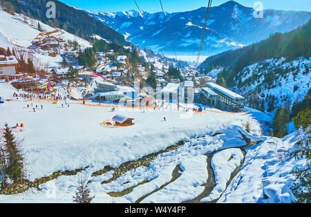 Schmittenhohenbahn cable car breath-taking journey with a view on snowy mountain river, Alpine slopes, pistes, forests and frozen Zeller see lake, Zel