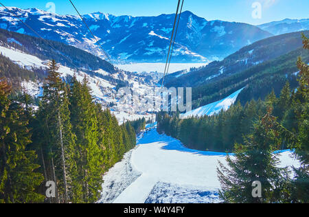 The interesting trip on Schmittenhohenbahn cable car with a view on Alpine snowy slopes, pistes, forests and frozen Zeller see lake in valley, Zell Am