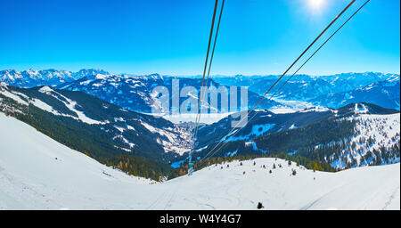 Panorama of fantastic Alpine scenery from the Schmitten mountain cable car, overlooking snowy mountains of Zell am See, pistes, coniferous forests, Ze - Stock Photo