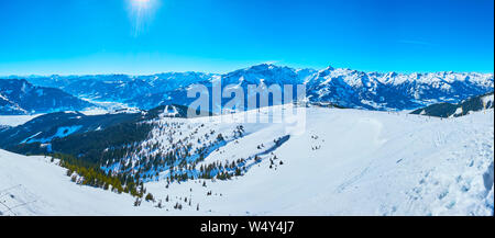 Observe the gentle snowy slopes of Schmitten mount with comfortable ski pistes and snowshoe routes, spruce forests and sharp rocks, Zell am See, Austr - Stock Photo
