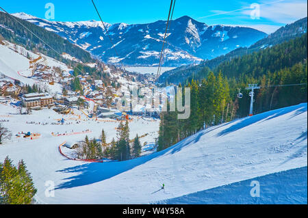 Aerial view on curved ski pistes, stretching along the snowy slope of Schmitten mount, lush coniferous forests and Zeller see valley with fozen lake a - Stock Photo