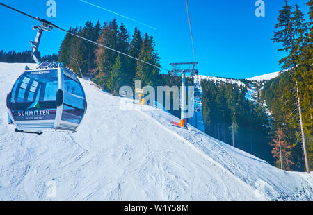ZELL AM SEE, AUSTRIA - FEBRUARY 28, 2019: The fast gondolas of Trassxpress cable car ride along the slopes of Schmitten mount, covered with wide ski r - Stock Photo