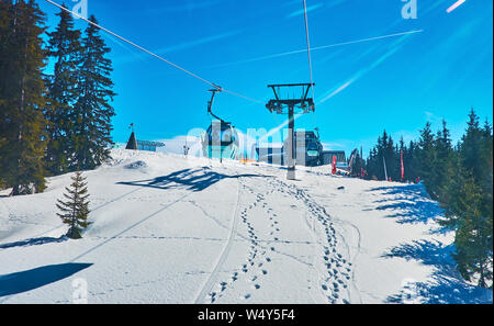 ZELL AM SEE, AUSTRIA - FEBRUARY 28, 2019: Enjoy the cableway journey over the snowy slopes of Schmitten mount in gondola of Areitbahn air lift, on Feb - Stock Photo