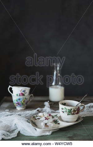 Delicate teacups stacked on top of on another and a matching plate. - Stock Photo