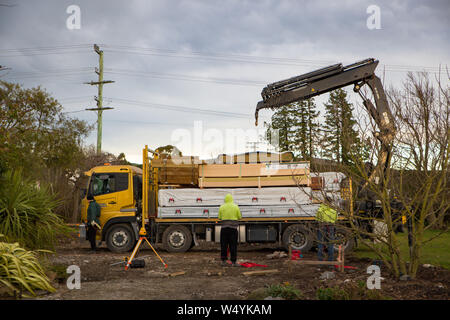 Sheffield, Canterbury, New Zealand, July 16 2019: A freight truck delivers building materials to construction site and the driver and builders unload - Stock Photo