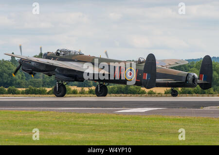 The Battle of Britain Memorial Flight Lancaster bomber back tracks along the runway at RNAS Yeovilton, UK after it's display on the 13th July 2019. - Stock Photo