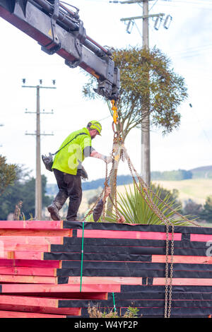 Sheffield. Canterbury, New Zealand, July 25 2019: Builders unload roof trusses that have been delivered by a Hiab truck to a building site - Stock Photo