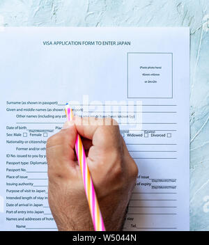 The person filling the Visa application form to enter Japan. - Stock Photo
