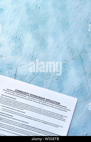 Filling community sponsorship application form on bright background - Stock Photo