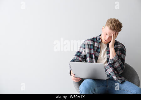 Tired young man with laptop sitting on chair against light background - Stock Photo