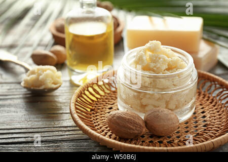 Jar with shea butter on wooden background - Stock Photo
