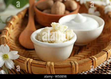 Bowls with shea butter and cream in wicker tray - Stock Photo