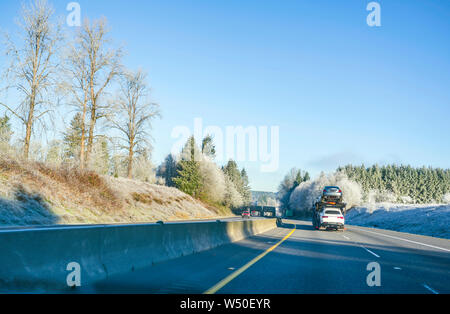 Big rig commercial grade professional car hauler semi truck transporting cars on the special two level semi trailer moving on the straight highway wit - Stock Photo
