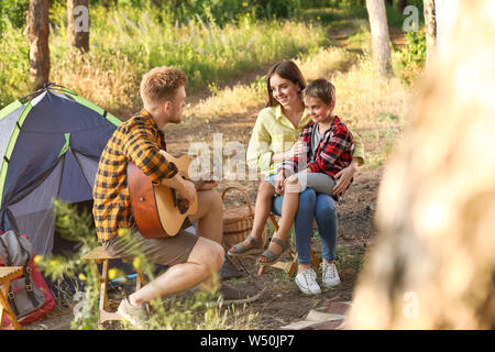 Happy family spending weekend in forest - Stock Photo