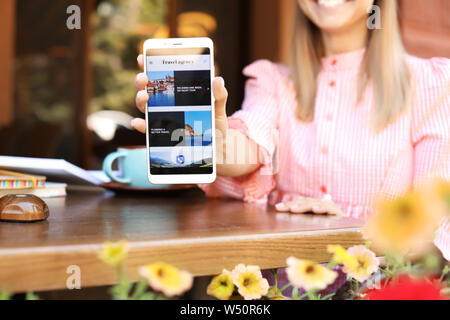 Woman with mobile phone visiting travel agency website while sitting in cafe - Stock Photo