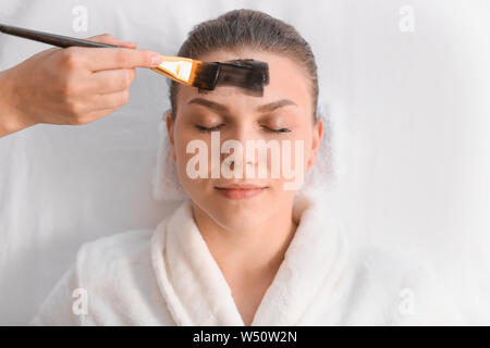 Beautiful woman undergoing treatment with facial mask in beauty salon - Stock Photo