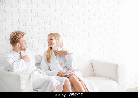Happy young couple in bathrobes sitting on sofa at home - Stock Photo