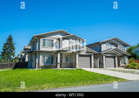 Residential duplex building with concrete drive ways and green lawns in front - Stock Photo