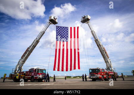 Personnel with Fire and Emergency Services, Marine Corps Installations Pacific - Marine Corps Base Camp Butler, hoist the American flag on Marine Corps Air Station Futenma, July 25, 2019. The personnel with Fire and Emergency Services were attending a practice for a change of command. U.S. Marine Corps Maj. Gen Paul Rock Jr. is scheduled to relinquish his post as Commanding General of Marine Corps Installations Pacific to U.S. Marine Corps Brig. Gen. William J. Bowers on July 26, 2019. (U.S. Marine Corps photo by Lance Cpl. Savannah Mesimer) - Stock Photo