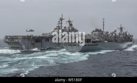 190714-M-QS181-1004 ARABIAN SEA (July 14, 2019) The amphibious assault ship USS Boxer (LHD 4) (left), receives supplies from the USNS Arctic (T-AOE-8) during a replenishment-at-sea. The Boxer Amphibious Ready Group and the 11th MEU are deployed to the U.S. 5th Fleet area of operations in support of naval operations to ensure maritime stability and security in the Central Region, connecting the Mediterranean and the Pacific through the Western Indian Ocean and three strategic choke points. (U.S. Marine Corps photo by Cpl. Jason Monty) - Stock Photo