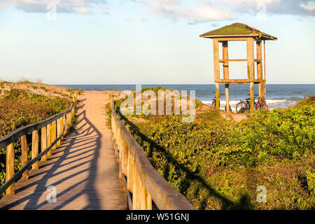 Lifeguard hut on Navegantes beach in the late afternoon, with wooden walkway over the dunes and native vegetation, blue sky with clouds - Stock Photo