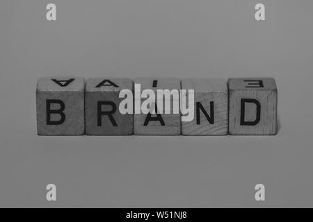 macro shot of wooden cubes on a table showing the word BRAND, Business