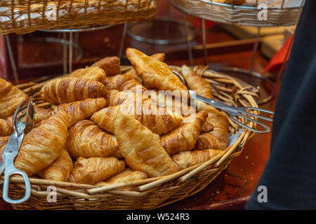 Pile of puffy and tasty croissants in the rattan basket - Stock Photo
