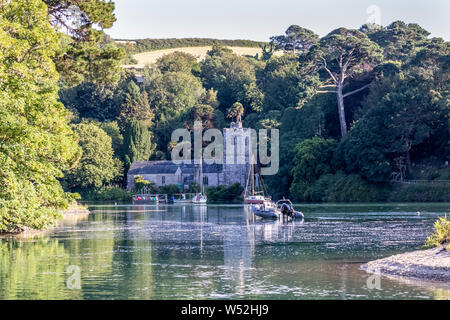 A high Spring Tide floods Saint Just in Roseland creek right up to the boundary  of the church - Stock Photo
