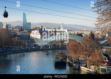 A cable car gondola hovers over the Mtkvari river. In the background: The Bridge of Peace from Michele De Lucchi. Downtown Tbilisi, Georgia, Caucasia - Stock Photo