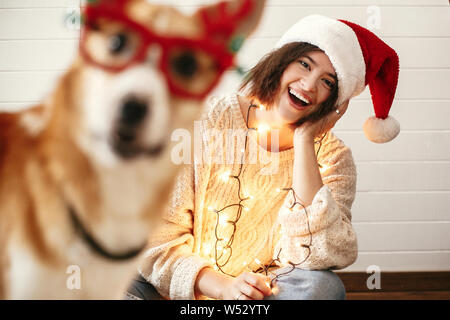 Stylish girl smiling in santa hat and christmas lights and looking at cute golden dog with funny emotions in festive reindeer glasses with antlers. Me - Stock Photo
