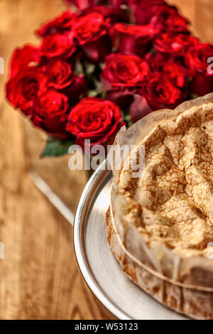 Portuguese traditional cake, sponge cake. on the wooden table with roses. - Stock Photo