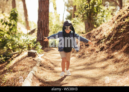 Cute boy with pilot goggles and hat running in forest. Kid pretending to be pilot playing in forest. - Stock Photo