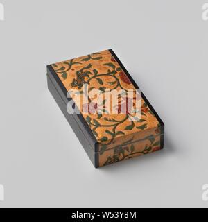 Cigarette box with gilt leather, Elongated cigarette box with lid of black lacquerware with inlaid gold leather with a decoration of stylized lion dogs (shishi) and peonies in green, red and gold on a beige background in a continuous band over the lid and sides, the inside with red mottled gold leather. Box and lid with a silver rim, two silver dividers inside. Signed on the inside of the lid with a seal in gold makie 'Yu'. Wooden box with op kar ak kinkarakawa botan karakusa maki tabako bako '(' cigarette box with gold leather with peony flower vines ') - Stock Photo