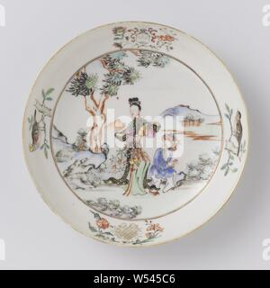Saucer with two Chinese ladies in a landscape, a coat of arms and a monogram, Porcelain dish, painted on the glaze in blue, red, pink, green, yellow, black and gold. On the shelf two walking Chinese ladies in a landscape with trees, mountains and a river, a lady has a flower vase in her hands. On the wall an unidentified family crest with three branches against a white background surrounded by scrolls and flower sprays. The helmet sign is also three branches. On the opposite side of the wall an unreadable monogram with flower sprays. Further on the wall twice a bird on a branch. Old label - Stock Photo
