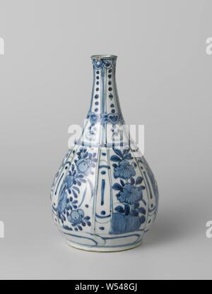 Pear-shaped bottle vase with flowering plants and dots in a panel decoration, Bottle-shaped porcelain vase with a pear-shaped body and a slightly spreading neck, painted in underglaze blue. The outer wall is modeled on the belly in wide and narrow rectangular compartments. In the broad compartments, each time a flowering plant on a rock, the narrow sections with stripes and dots. Narrow, rectangular pockets on the neck with beaded hangers with tassels. The sections are interrupted by a band with ruyi motifs. On the outside edge a band with flowers in medallions. A decorative band around - Stock Photo