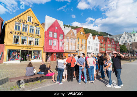 BERGEN, NORWAY - JULY 28, 2018: Tourists in front of the historical buildings in Bryggen- Hanseatic wharf. Bryggen has been on the UNESCO World Herita - Stock Photo