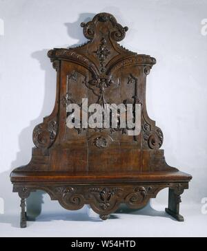 Garden bench in Marot style, Bank of stained pine. The narrow seat rests on cheeks and has a scalloped decorative piece with broken volutes, a symmetrical leaf motif with branches in the middle and brushes on the corners. The high back has a midfield, sculpted above and below, which shows relief trophies, hung on ribbons, above which turned-down knot motifs are tied together from below. Volute consoles inserted on either side. To crown acanthus leaves in the middle of two devoted broken volutes., Hunting trophies, hunting, chase (hunting weapons, equipment, outfit), ornament derived from plant - Stock Photo