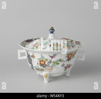 Terrine with lid, multicolored painted with a decor after Japanese example, Terrine with lid made of painted porcelain. The round terrine stands on three legs and has two square ears. The lid has a gold-plated button. The terrine is painted on both sides with a Chinese lady with a flower branch in hand and with bound hedges and plants. The lid is painted with a walking figure, bound hedges, a lion and flowers. The terrine is not marked., Meissener Porzellan Manufaktur, Meissen, c. 1725 - c. 1730, porcelain (material), h 14.2 cm h 9.5 cm w 18.2 cm × d 17.5 cm h 6 cm × d 14.6 cm - Stock Photo