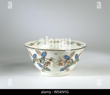 Sink bowl, decorated with rose branches in relief, multicolored painted, Sink bowl from Böttger porcelain. The bowl has a stand ring and a slightly bent mouth edge. The wall is decorated with appliqued rose branches, between which birds, butterflies and insects are painted. The bottom of the bowl is painted with a kakiemon motif, consisting of prunus branches on rocks and two birds. The mouth rim is trimmed with a brown trim. Along the inside of the edge are symmetrical green tendrils with red flowers painted in the middle. The appliqued rose branches are also painted, and damaged areas have - Stock Photo