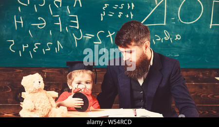 Boy, child on calm face holds alarm clock while teacher talk to kid. Teacher with beard, father teaches little son in classroom, chalkboard on background. Individual lesson concept. - Stock Photo