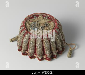 Fair of wine red velvet embroidered in gold, silver thread and multicolored silk with an unidentified alliance weapon, silver thread and multicolored silk with an unidentified alliance weapon. Model: The flat round bottom has a wavy raised edge with holes through which a cord of yellow and red silk - ending in a button with wooden core covered with yellow silk and metal wire - is drawn. Halfway two buttons - with a core of wood wound with silk - are sewn on the edge. Lined with goat leather. Decoration: the 20 bulges or 'ribs' are decorated with long stacked ornaments with lobes on - Stock Photo