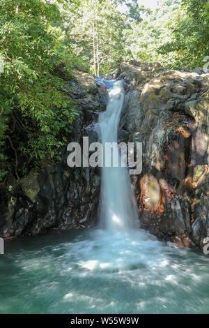 Kroya waterfall in Sambangan mountain area on Bali island. The pools with crystal clear water under the rocky wall creates harmonious atmosphere. - Stock Photo