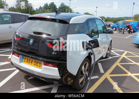 Charging your electric car at the motorway services with ecologically produced electricity for cheap oil free motoring that does not cost the planet - Stock Photo