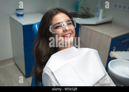 smiling young brunette woman patient lying on dental chair wearing safety glasses under the medical lamp in clinic - Stock Photo