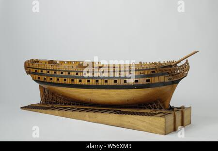 Model of a 74-Gun Ship on a Slipway, Construction model or the hull of a 74-piece line ship in the ropes on a slope, using the French launch method The skin is omitted on the port side under the barwood and on the starboard side above the barwood, on starboard a piece of skin with trusses can be removed in three places. Sixty-seven artillery ports spread over three decks, plus eight places for artillery firing. The galleon is only worked out on the port side: the figurehead is a woman in Roman robe with a laurel wreath in her hand. Twisted mirror with two gates in the wulf, the one-storey - Stock Photo