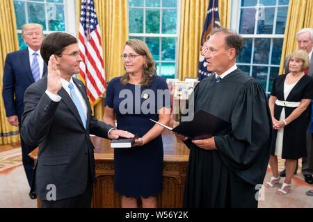 U.S Secretary of Defense Mark Esper, left, takes the oath of office from Supreme Court Associate Justice Samuel Alito as his wife Leah Lacy, center, looks on, during a ceremony in the Oval Office of the White House July 23, 2019 in Washington, DC. - Stock Photo
