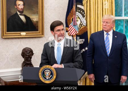 U.S President Donald Trump watches as new Secretary of Defense Mark Esper delivers remarks in the Oval Office of the White House July 23, 2019 in Washington, DC. - Stock Photo